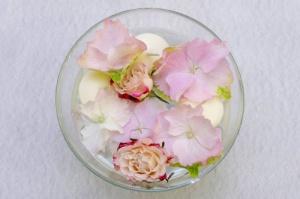 miska s květinami a plovoucími svíčkami